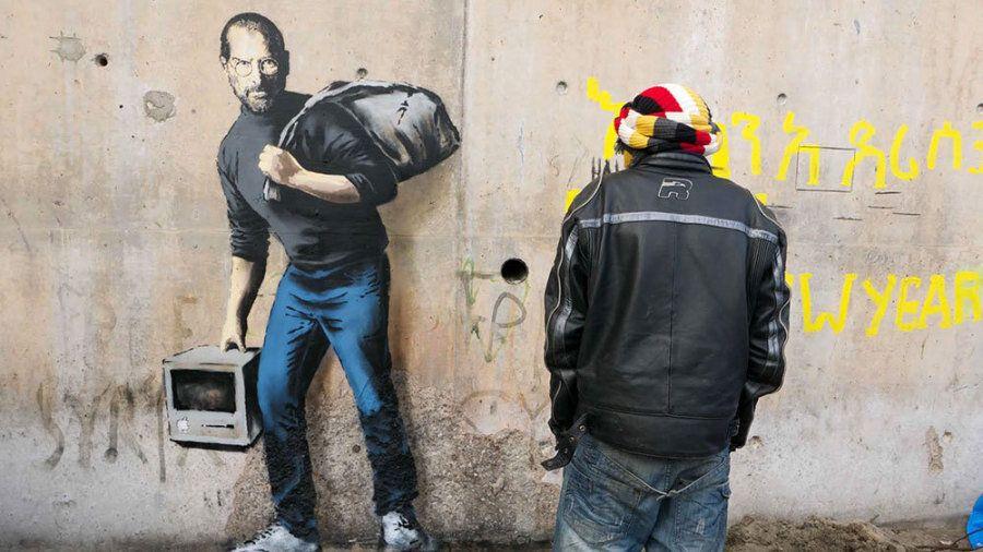 Banksy ricorda al mondo che Steve Jobs era figlio di un migrante siriano. I suoi graffiti a