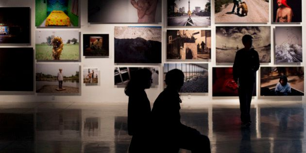 In this Sept. 24, 2015 photo, visitors look at images inside the recently opened Foto Museo Cuatro Caminos...