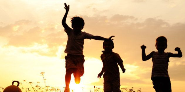 Silhouette, group of happy children playing on meadow, sunset,