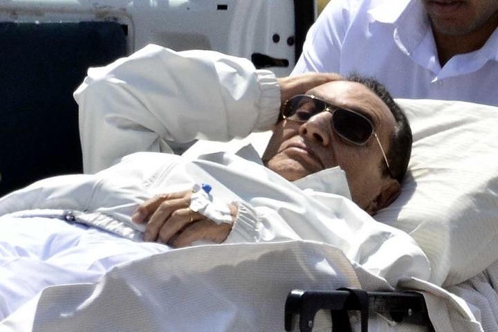 Ousted Egyptian president Hosni Mubarak (C) is wheeled out of an ambulance outside the Maadi military hospital following a he