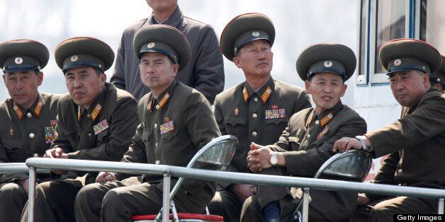 SINUIJU, NORTH KOREA - APRIL 10:  (CHINA OUT) North Korean military officers sit onboard a ship at the frontier between China