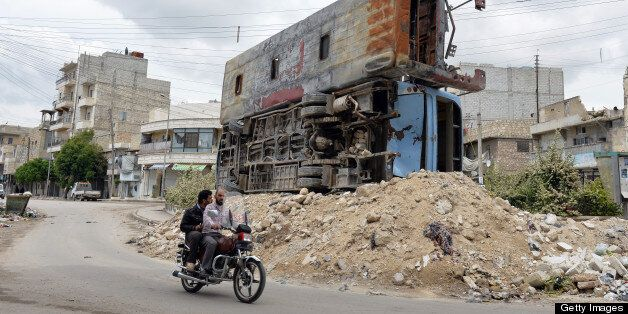 Syrian civilians ride past  two destroyed buses piled up on rubble in the northern city of Aleppo on April 22, 2013. The Euro