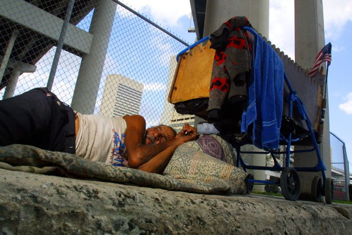 397550 01: Belede Martinez, who is homeless, sleeps November 20, 2001 on a sidewalk in Miami, Florida. Nearly one third of th