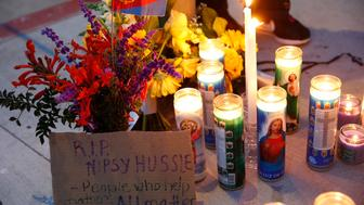 A sign for rapper Nipsey Hussle is left by candles set up across from a clothing store owned by Hussle in Los Angeles, Sunday, March 31, 2019. Hussle, the skilled and respected West Coast rapper who had a decade-long success with mixtapes but hit new heights with his Grammy-nominated major-label debut album in 2018, has died. He was 33. (AP Photo/Damian Dovarganes)