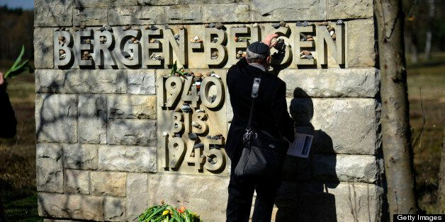 A man puts down a stone at the memorial site in Bergen-Belsen, northern Germany, during the ceremony to mark the 65th anniver
