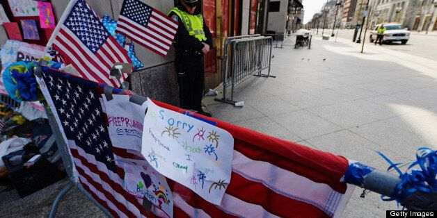 BOSTON, MA - APRIL 22:  A Boston Police officer bows his head during a moment of silence near the Boston Marathon finish line