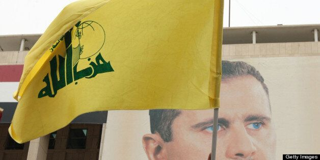 Syrian demonstrators hold up a Lebanese Hezbollah flag in front of a portrait of President Assad, during a rally to show thei