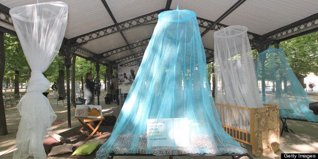 People look at the 'Mosquito nets for life' exhibition, displaying photographhies and mosquito nets, in the Luxembourg garden