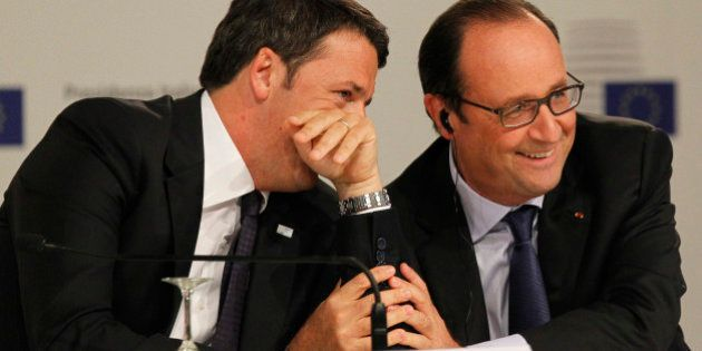 Italian Premier Matteo Renzi, left, and France's President Francois Hollande smile during a press conference...
