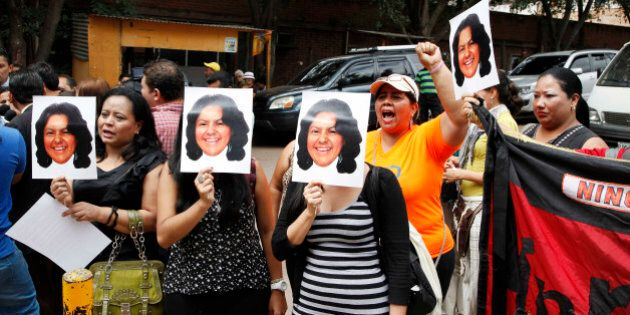People hold up photos of slain Honduran indigenous leader and environmentalist Berta Caceres outside...
