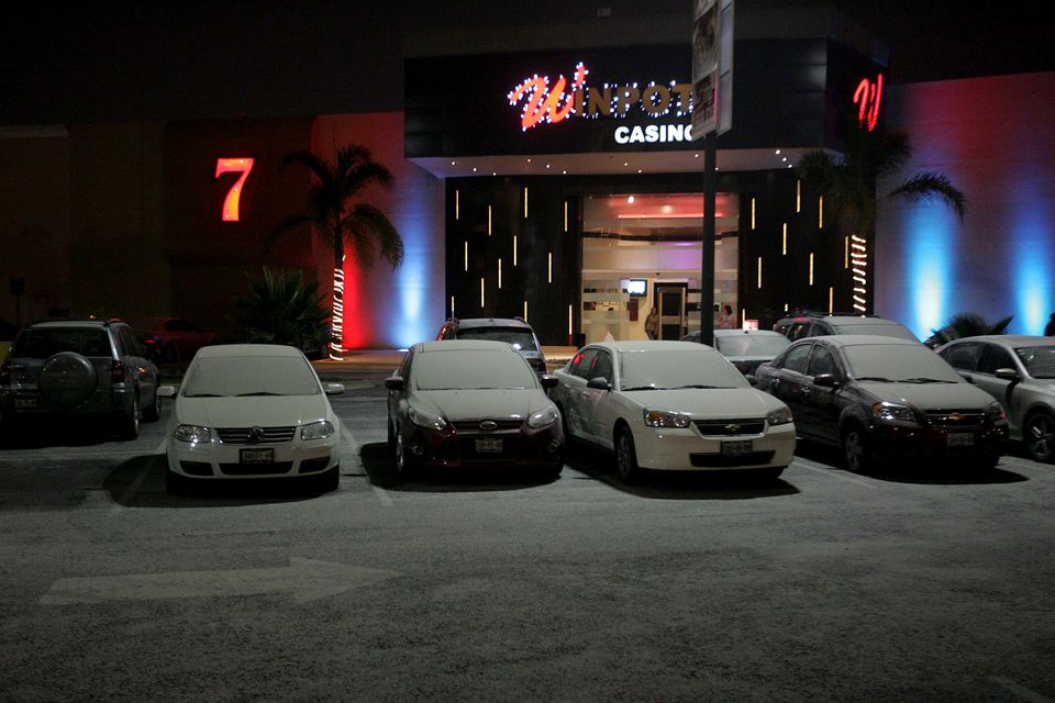 Cars dusted with volcanic ash sit parked in a casino parking lot in Puebla, Mexico, Tuesday night, May 7, 2013. The Popocatep
