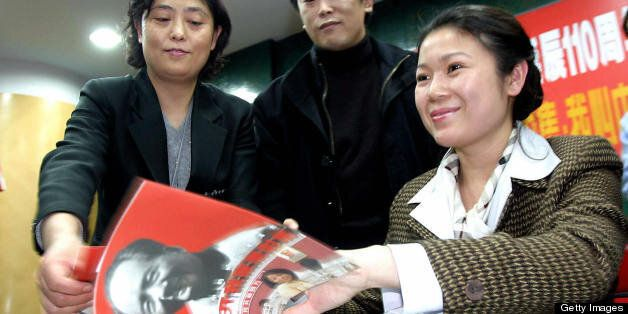 BEIJING, CHINA:  Granddaughter of the late Chinese revolutionary Mao Zedong, Kong Dongmei (R) signs copies of the new pictori