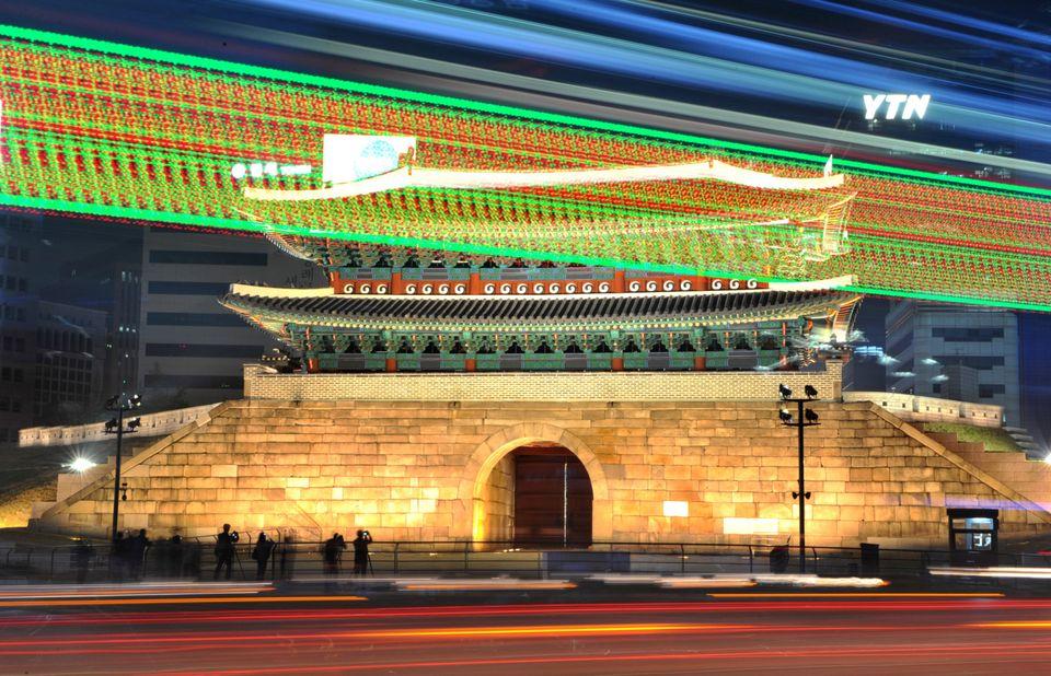 A long exposure photograph shows traffic commuting at night near South Korea's landmark Namdaemun gate in Seoul on May 4, 201