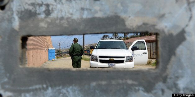 A US Border Patrol agent, seen through an opening in a fence, keeps watch on the 'border fence' near the San Ysidro port of e