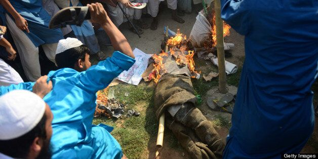 Supporters of Islamic political parties burn and kick an effigy of a blogger inside a madrasa during a nationwide strike in D