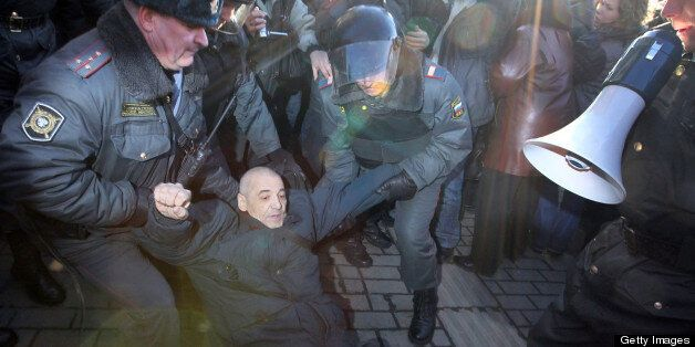 Russian riot police officers detain an opposition supporter during a rally to defend Article 31 of the Russian constitution,