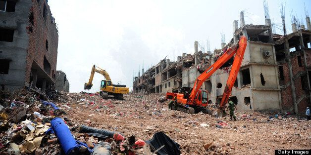 Excavators clear debris as Bangladeshi rescue and army personnel continue recovery operations at the site of the eight-storey