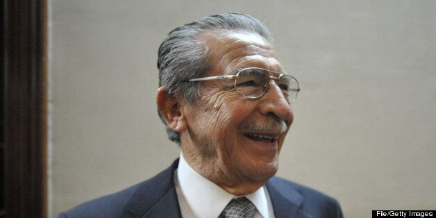 Former dictator and current lawmaker Efraín Ríos Montt smiles as he remains in a room of the Public Ministry to check whether