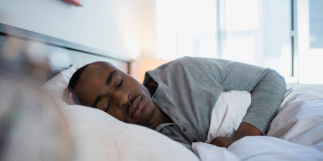Serene man sleeping in bed in the