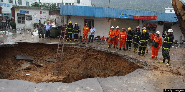 SHENZHEN, CHINA - MAY 21:  (CHINA OUT) Rescuers search for people buried in a road cave-in accident site on May 21, 2013 in S