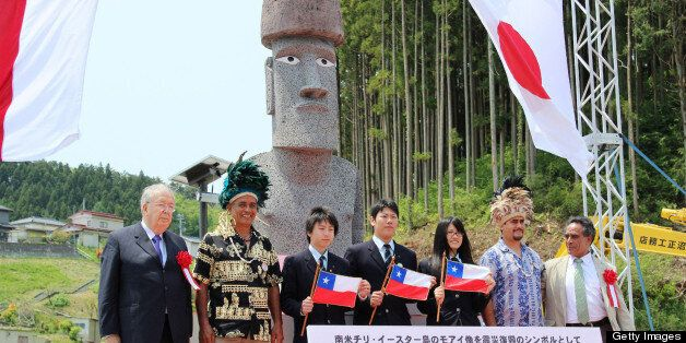 Japanese high school students and carvers from Chile pose before a new 'Moai' statue (back C), modelled on the mysterious car