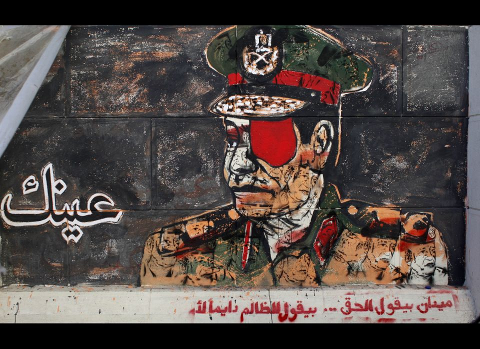 "Graffiti depicting a high ranking army officer with an eye patch and Arabic writing that reads, ""your eye, the square says th"