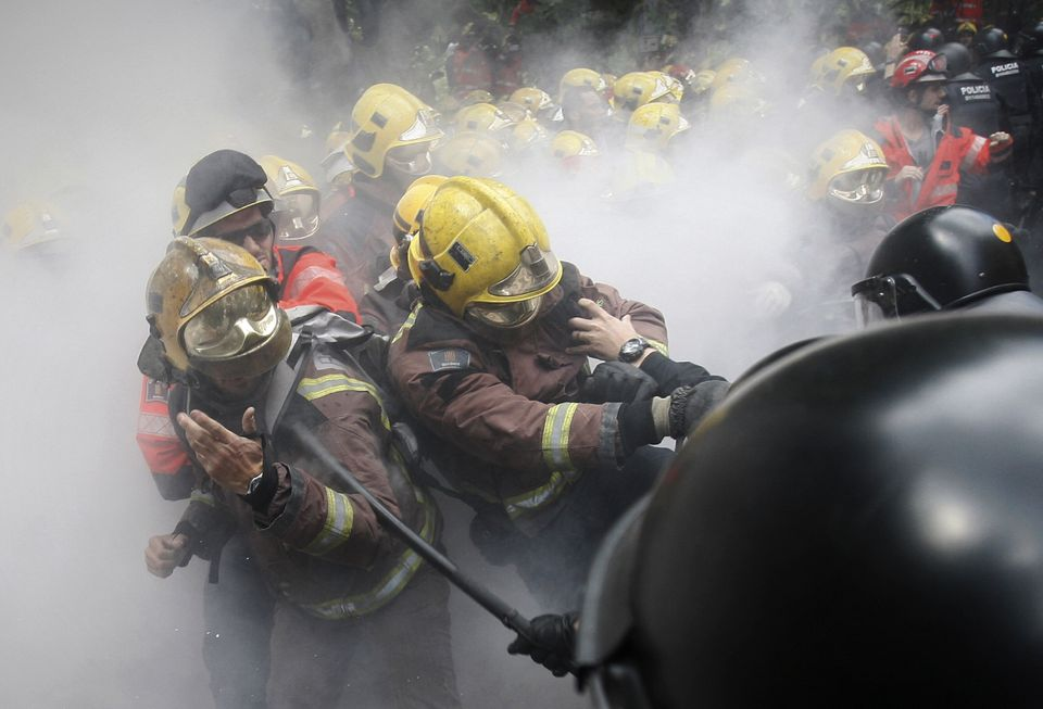Riot police charge at firefighters during a protest against austerity measures in front of the Catalan Parliament in Barcelon