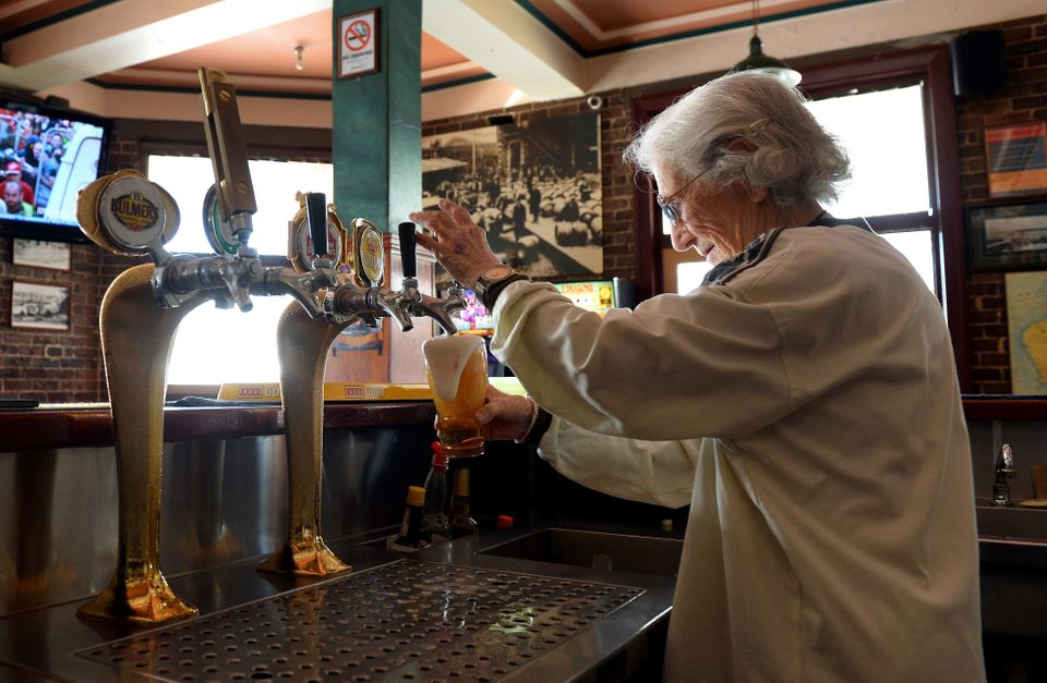In a picture taken on May 14, 2013, Sydney's oldest barmaid Lil Miles pulls a beer at her family's Bells Hotel in Woolloomool