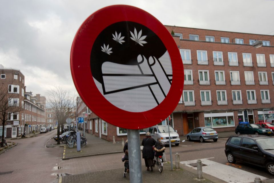 Mothers and their children leave a nearby school as a sign prohibiting the use of marijuana in a designated area is seen in A