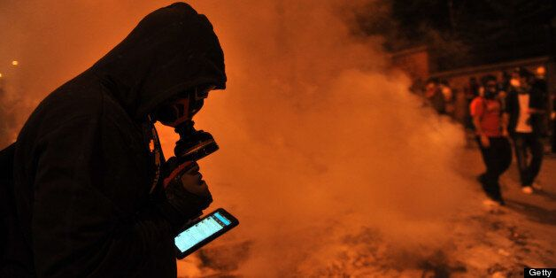 A protestor uses Facebook on mobile phone to give latestt news about the clashes near Taksim in Istanbul on June 3, 2013 duri