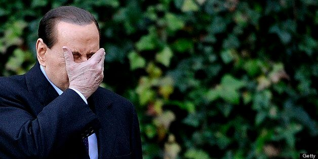 Italian Prime Minister Silvio Berlusconi holds his face in his hand at the Villa Madama in Rome as he arrives for a meeting w