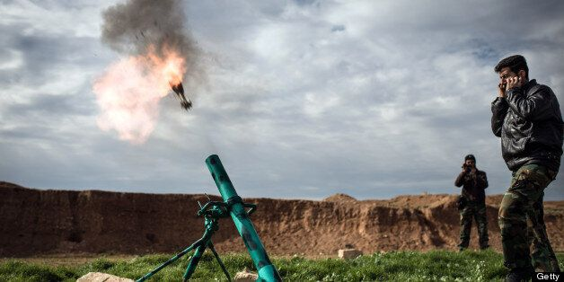 Syrian rebels fire a mortar towards regime forces stationed at Kwiriss airport in Al-Bab, 30 kilometres from the northeastern