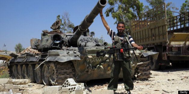 A Rebel fighter poses infront of a tank reportedly confiscated from an army barracks in the northwestern Syrian city of Sermi