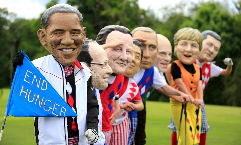 Members of the NGO group Oxfam, dressed in golf clothes and wearing paper mache masks, imitate G-8 leaders during a demonstra