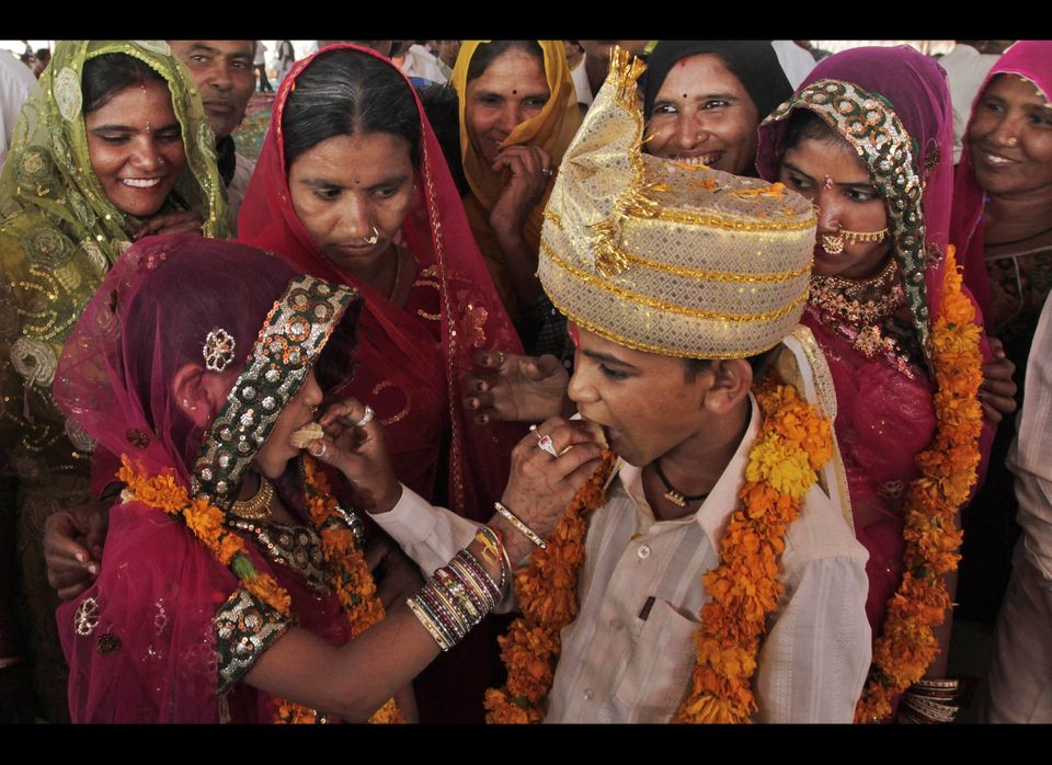 A young Indian bride and her groom share sweets during a wedding organized by a local agency in the village of Vadiya, about