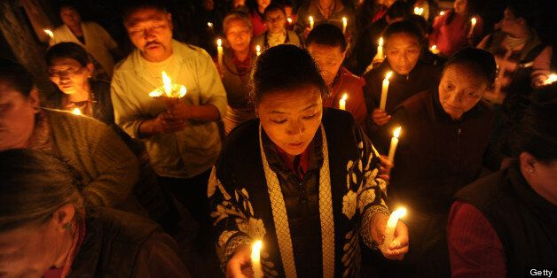 Tibetans-in-exile take part in a candlelight vigil following the self-immolation attempt by a monk earlier today, marking the
