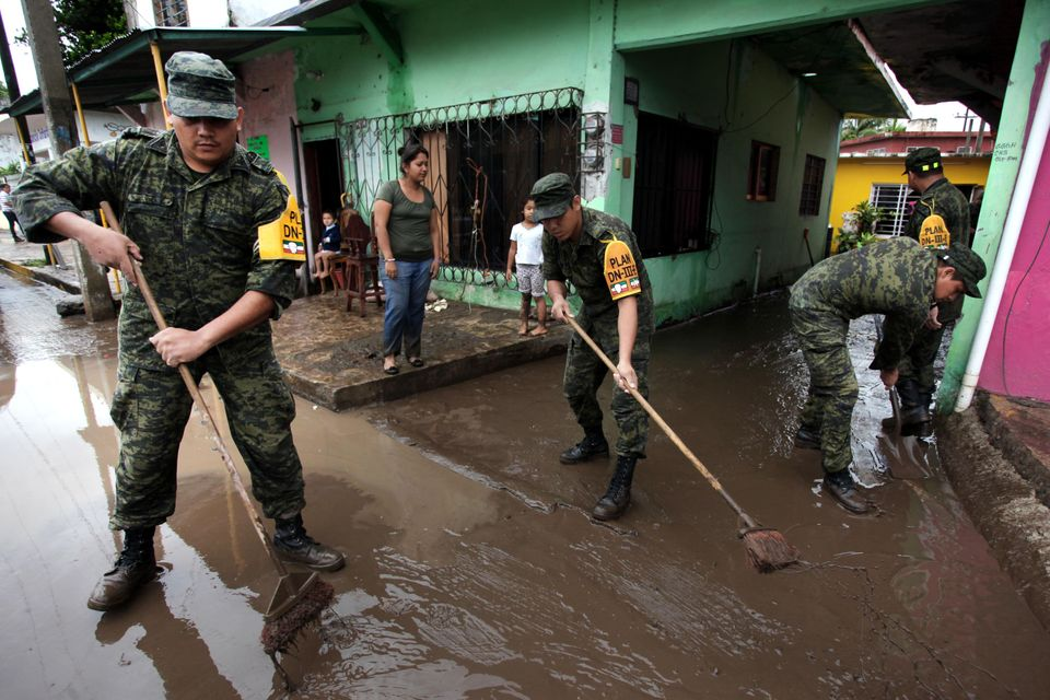 Soldiers sweep away mud from an area that was flooded by heavy rains caused by Tropical Storm Barry in the Ursulo Galvan muni