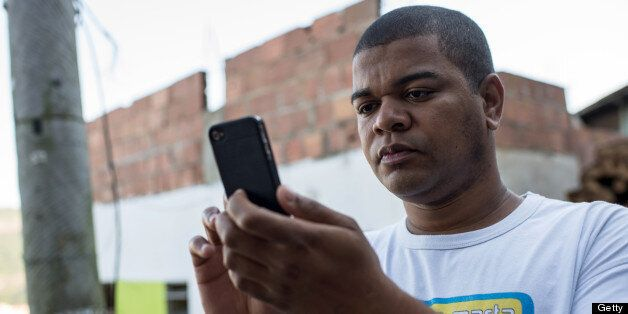 Favela tour guide Thiago Firmino takes a picture with his cell phone in Santa Marta shantytown in Rio de Janeiro, Brazil, on