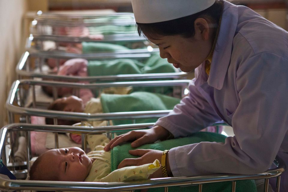 A North Korean nurse comforts a baby at a nursery inside Pyongyang Maternity Hospital in Pyongyang, North Korea on Wednesday,
