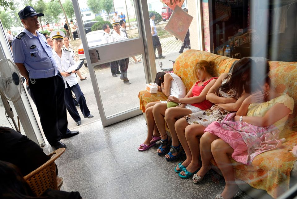 This photo taken on June 21, 2011 shows Chinese police (L) watching over a group of massage girls suspected of prostitution d