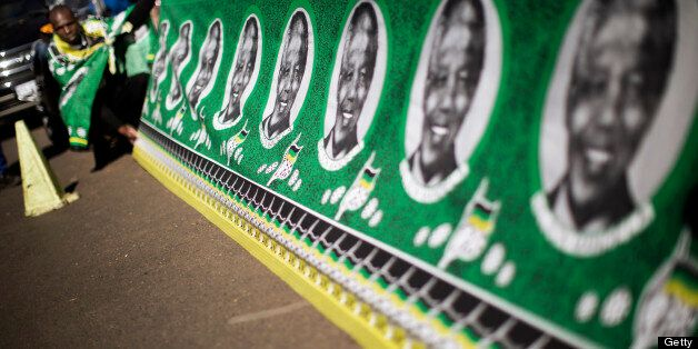 Street vendors display a large traditional fabric with portraits of South African President Nelson Mandela and ANC flags outs