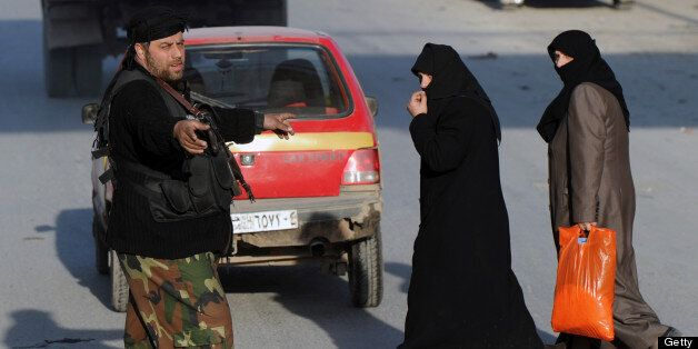 A Syrian rebel fighter helps women cross the road at a check point in Aleppo's old city on January 16, 2013. Syria's transpor