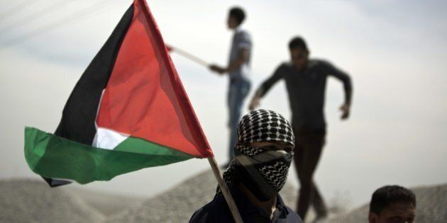 A Palestinian demonstrator holds the national flag during clashes near the border with Israel, east of...