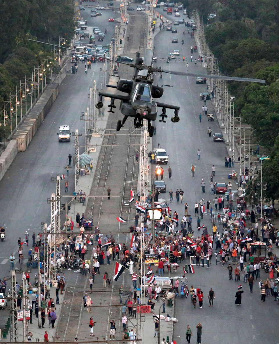 A military attack helicopter flies over a street near the presidential palace, in Cairo, Egypt, Friday, July 5, 2013. (AP Pho