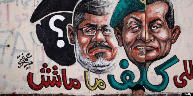 CAIRO, EGYPT - JULY 3: An opposition demonstrator sits below graffiti of Egyptian President Mohammed Morsi on the walls of Eg