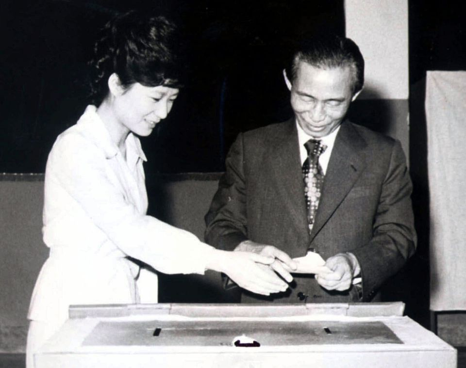 In this 1977 file photo, then South Korean President Park Chung-hee, right, and his daughter, Park Geun-hye, cast ballots in