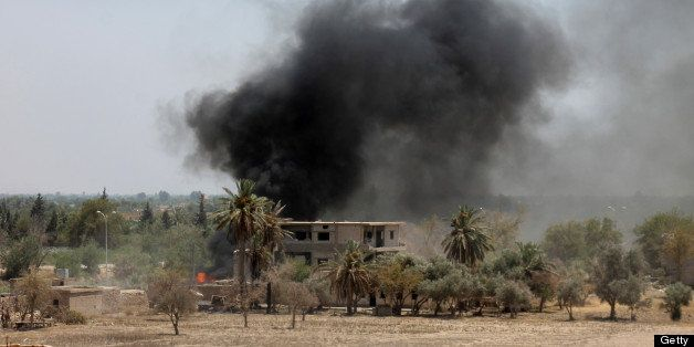 A picture taken on July 18, 2013 shows smoke rising from a building after opposition forces attacked a government forces held