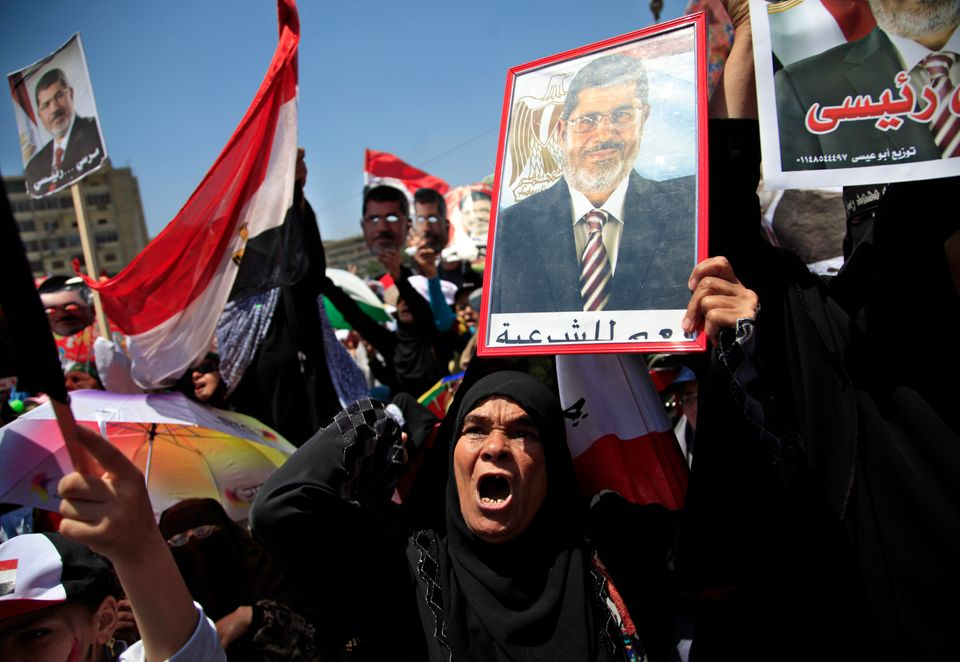 Supporters of Egypt's ousted President Mohammed Morsi hold pictures of him and chant slogans during a protest at Nasr City, w