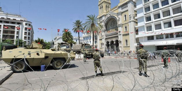 Tunisian soldiers stand guard on the fringes of an anti-government demonstration on the Habib Bourguiba Avenue on July 26, 20