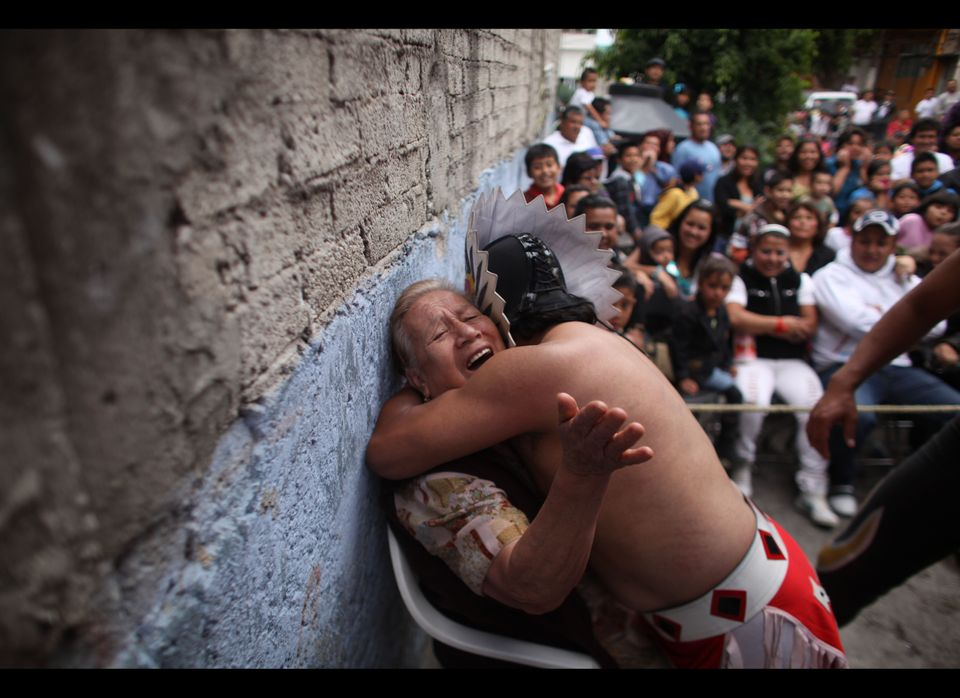 In this photo taken May 13, 2012, Mexican Lucha Libre wrestler Mixteco Jr., hugs an elderly woman during a Caravan Super Tari